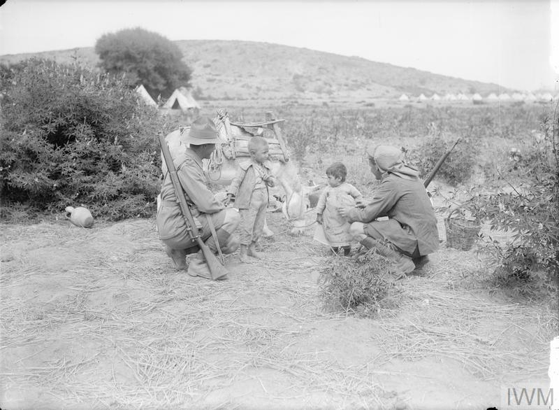 An Australian soldier and a man of the New Zealand Mounted Rifles Brigade make friends with two little children on Lemnos.