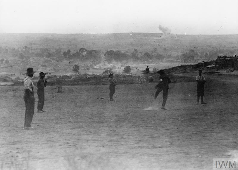 "Men of the Australian Army Medical Corps playing football in the evening. A shell of the ""evening hate"" (shelling by the enemy in the evening) is seen bursting in the background. The highest ground to the right on the horizon (not shown in this print) is Achi Baba."