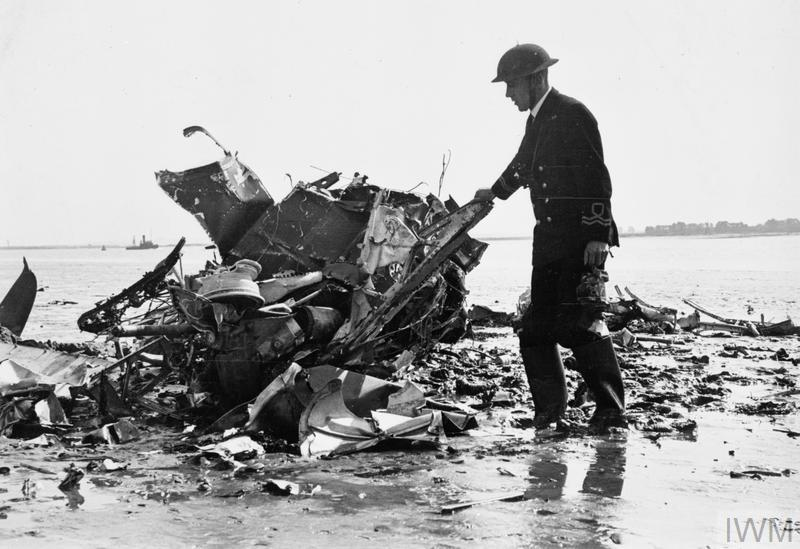 An RNVR officer of the Medway River Patrol inspects the wreckage of a Spitfire that came down on mudflats in early September 1940. Although not positively identified, the aircraft may have been a No 66 Squadron machine, shot down by Me109s over the Medway on 5 September. Pilot Officer P. King baled out, but his parachute failed to open.