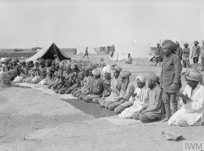 A line of Islamic Indian troops knelt down and in prayer at their camp, part of which can be seen in the background.