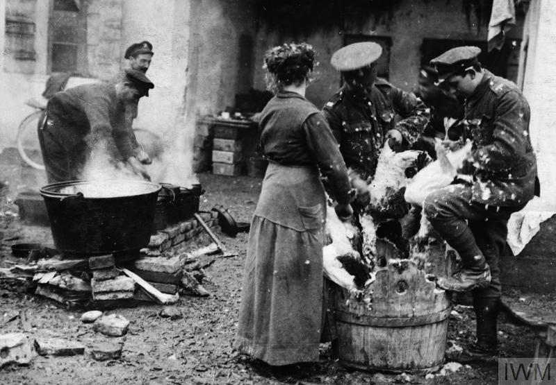 An Italian woman helping British troops to pluck turkeys for their Christmas dinner, December 1917.