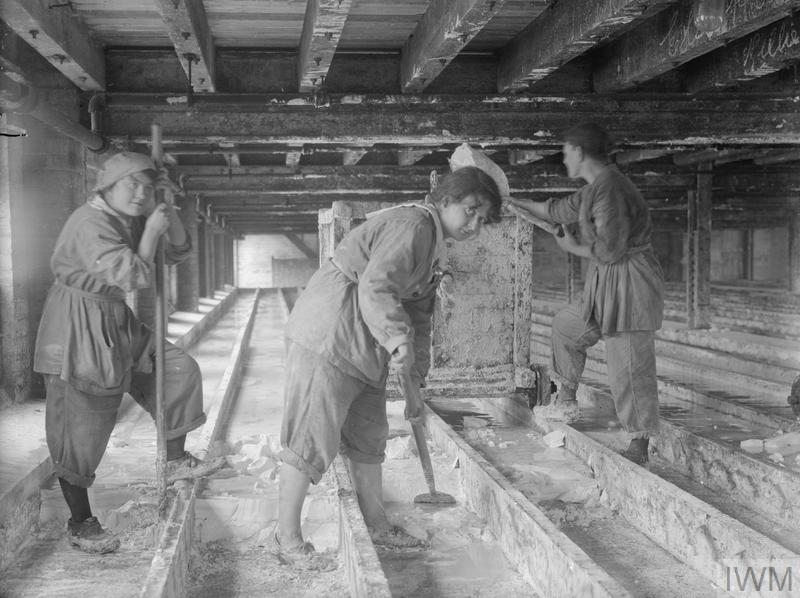 Female workers scraping runs and shovelling starch into trucks at the glucose factory of Nicholls, Nagel & Co. Ltd., Trafford Park, Manchester, September 1918.