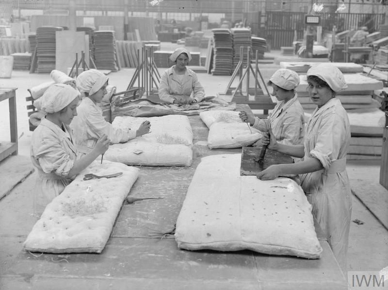 Female workers sewing and buttoning asbestos mattresses (used for lining boilers in battleships) in Turner Bros., Asbestos Factory, Trafford Park, Manchester, September, 1918.