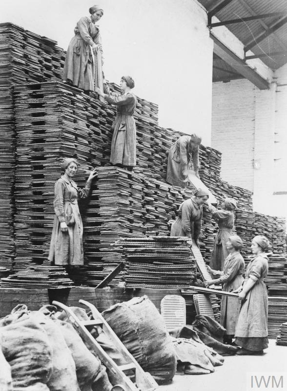 Female workers stacking oil cakes at a Lancashire oil and cake factory, September, 1918.