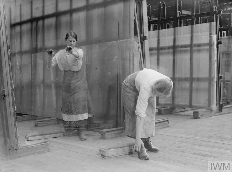 Female workers carrying a sheet of drawn glass from the lehr table in a Lancashire glass factory, September 1918.