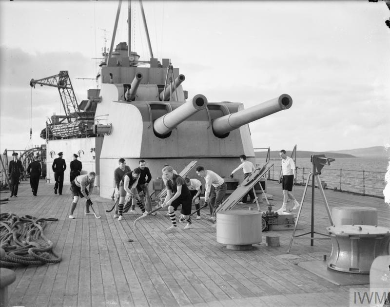 Officers of HMS KENT enjoying a free for all game of deck hockey under the shadow of the cruiser's 8 inch guns. Whenever possible the game is played for exercise each afternoon both at sea and in port.
