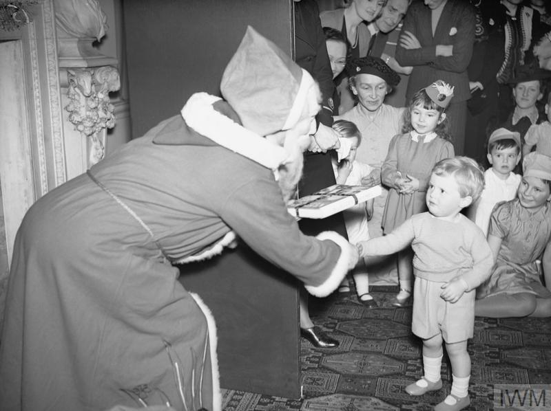 'Father Christmas' presenting Winston Churchill's grandson with a gift at a Christmas party for Allied naval officers' children.