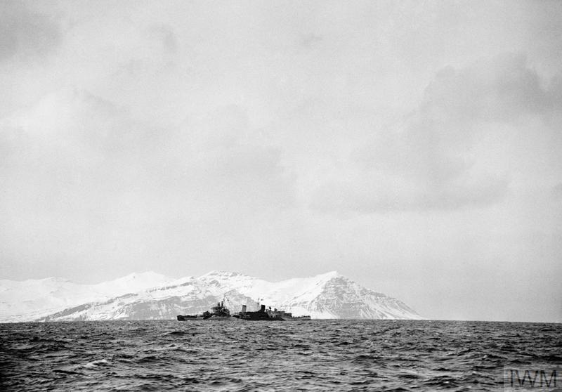 HMS Belfast silhouetted against a large iceberg during her service with the Arctic Convoys