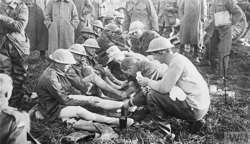 Australian troops: Men of the 10th Brigade who had been in the front line trenches for several days have a foot inspection at Dragon Farm.