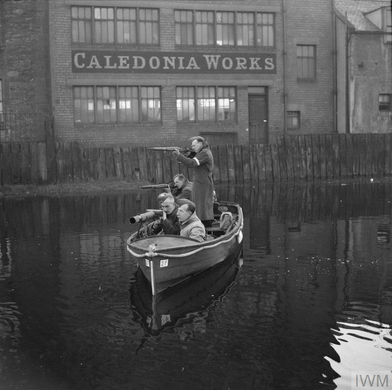 Home Guards patrol a section of canal in Edinburgh in a motor boat armed with rifles and a mounted Lewis gun, 19 October 1940.