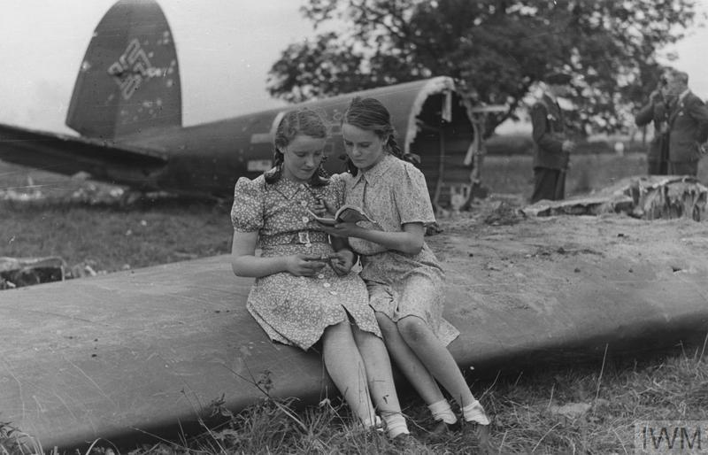 Schoolgirls sitting on part of a Nazi bomber which crashed near their farmhouse.