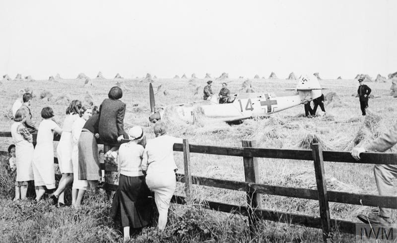"Locals watch as troops and police inspect Messerschmitt Bf 109E-1 (W.Nr. 3367) ""Red 14"" of 2./JG52, which crash-landed in a wheatfield at Mays Farm, Selmeston, near Lewes in Sussex, 12 August 1940. Its pilot, Unteroffizier Leo Zaunbrecher, was captured."