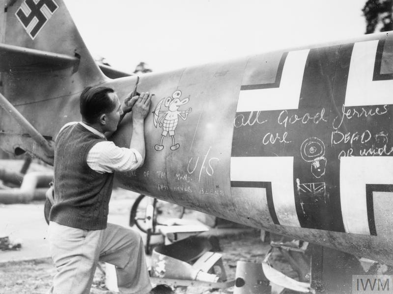A member of staff at a technical college preparing to remove the 'Mickey Mouse' staffel emblem from the rear fuselage of a shot-down Messerschmitt Bf 109E4, 'Red 2', of 3./LG 2, 2 October 1940.