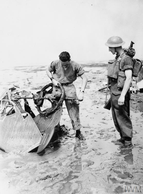 Soldiers examine an MG 15 machine gun and part of the tail assembly of a German Dornier Do 17Z bomber of the KG 2, shot down over the Thames Estuary during attacks on Eastchurch aerodrome, 13 August 1940.
