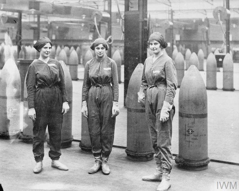 Three female munitions workers stand in front of 15-inch high explosive shells at the National Shell Filling Factory at Chilwell, Nottinghamshire, during the First World War.