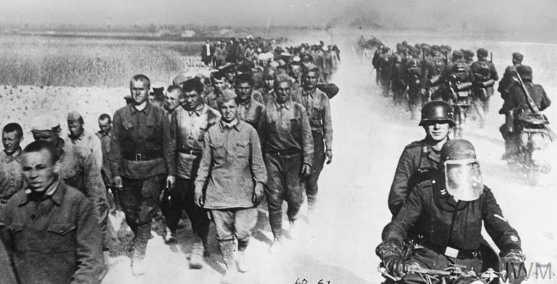 German motorcycle troops and infantry pass a long column of Russian prisoners during the advance into the Soviet Union, 1941.