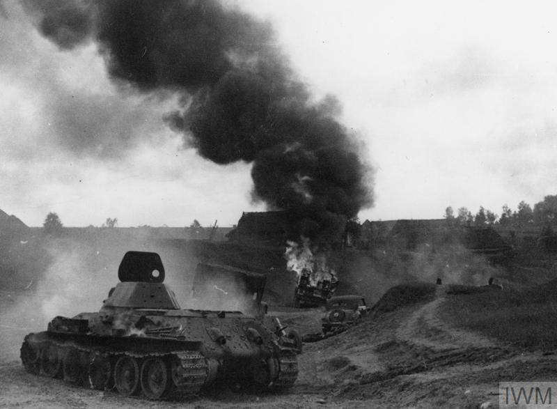 A knocked-out Soviet T-34 tank and burning vehicles on a road in Russia.