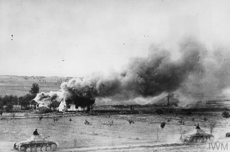 German PZKPFW II tanks advance past a burning Russian village.
