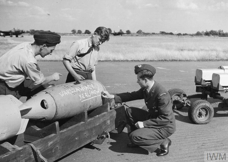 Groundcrew of a Polish Air Force bomber squadron, very likely of No. 300 Squadron, scribbling their best wishes to the enemy on a bomb at RAF Hemswell, 15 August 1941. The inscription in Polish reads: 'Warszawiacy Berlinowi - From Varsovians for Berlin'.