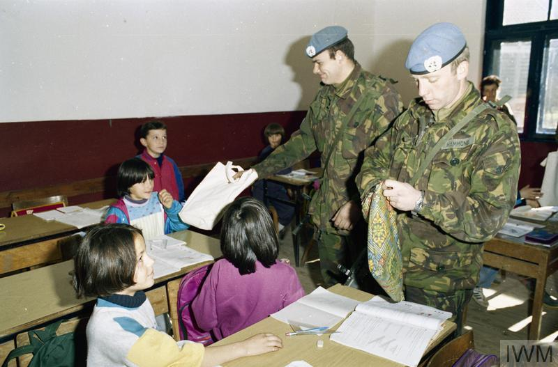 Members of the Household Cavalry Regiment handing out books to the children of a school in Lug, near Prozor