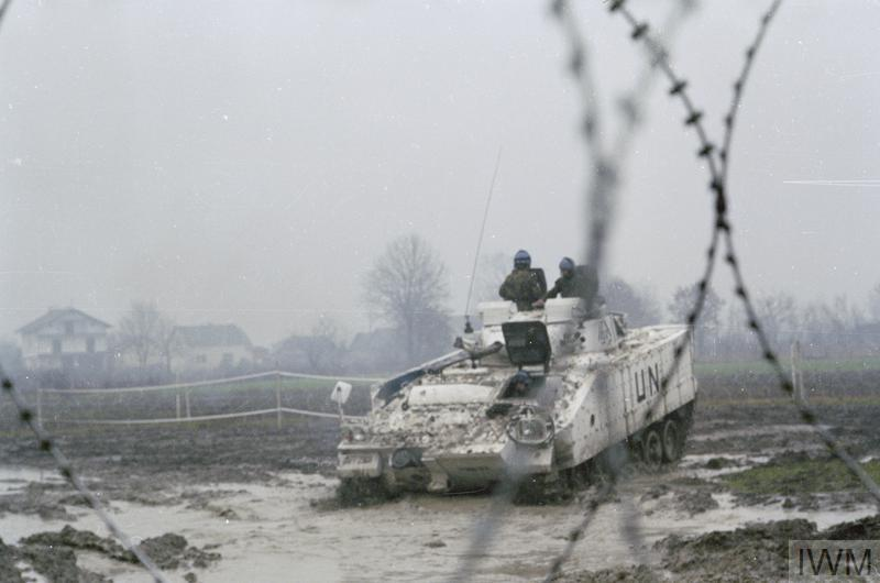 Troops of the 1st battalion Royal Highland Fusiliers in Jelah, North of Maglaj, Central Bosnia. A Warrior FV510 can be seen through barbed wire navigating the mud.