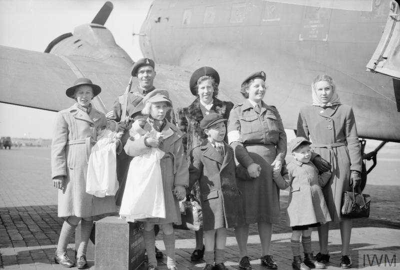 British soldiers and their families standing in front of a plane during the Berlin Blockade 1949