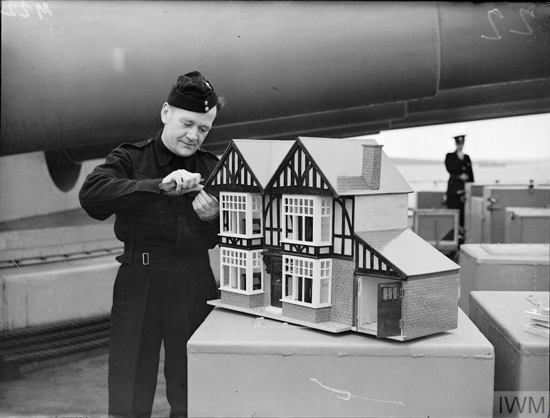 Royal Marine J Lynch putting the finishing touches on a large doll's house, complete with furniture.