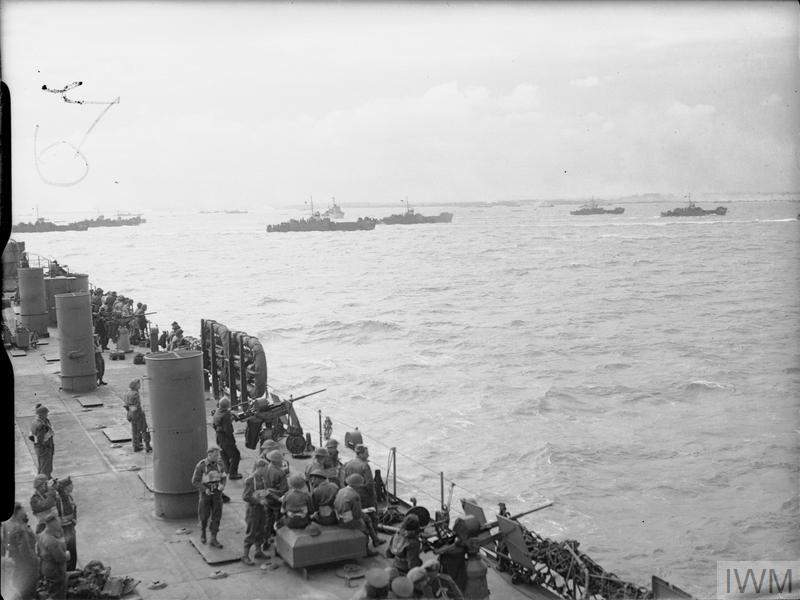 British troops and US sailors manning 20mm gun positions on board USS LST-25 watch LCI(L) landing craft head towards the beaches of Gold assault area, 6 June 1944.