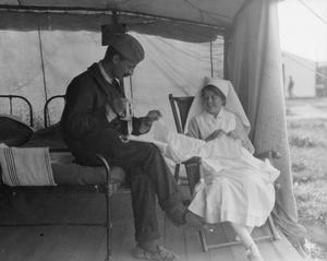 A nursing sister of a Scottish Women's Hospital unit teaches a French patient to sew, Salonika, 1916. THE SALONIKA CAMPAIGN 1915 - 1918