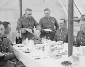 Captain Davis, Officer Commanding No. 706 Motor Transport Company (ASC) carves the Christmas turkey for his officers in their tented Mess, Christmas Day 1916. No. 706 MT Company was one of a number of support units attached to the Serbian Third Army during the Salonika Campaign.