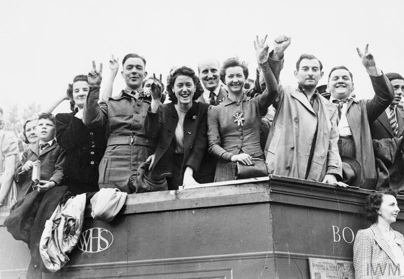 Revellers give the V-Victory sign as they celebrate VE Day outside the Houses of Parliament.