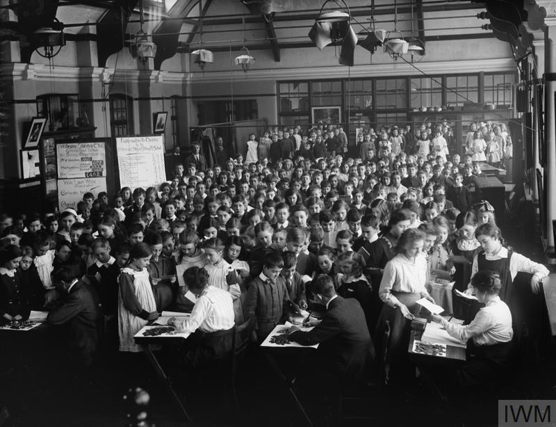 Pupils pay their weekly contributions into the War Savings Association in 1916 at Gibbons Road School, Willesden, London.
