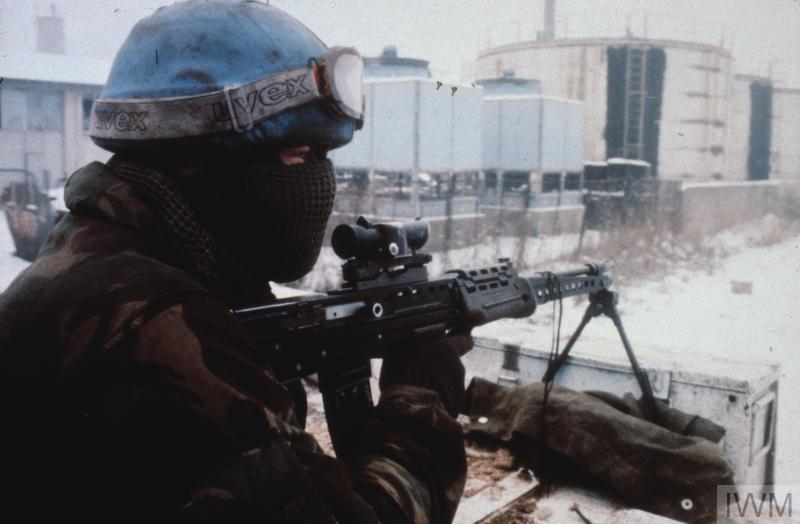 A British soldier, his face muffled against the cold, keeps watch with his assault rifle from the top of a 432 armoured personnel carrier as it moves through snow covered landscape during Operation LUMBERJACK in early 1993. The operation was to escort urgently needed convoys of firewood into Sarajevo.