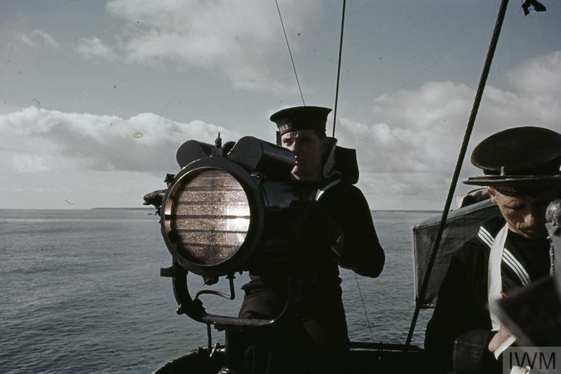 A signaller operating a 10-inch signal lamp on board a British warship.