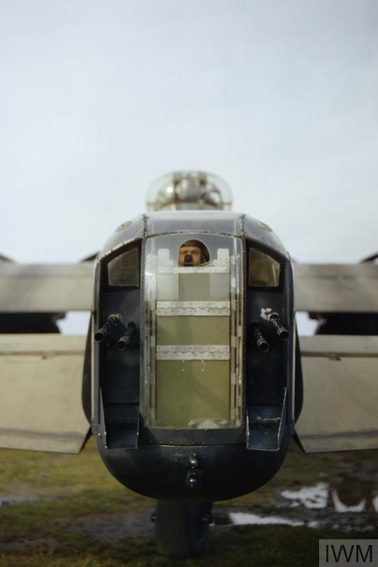 A gunner, believed to be Sergeant J Bell, looks through the opening in the perspex of the rear turret of Avro Lancaster R5740/`KM-O'. The four guns shown are Browning .303 machine guns.
