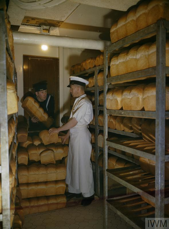 A naval rating collects bread for his mess from the battleship's bakery.