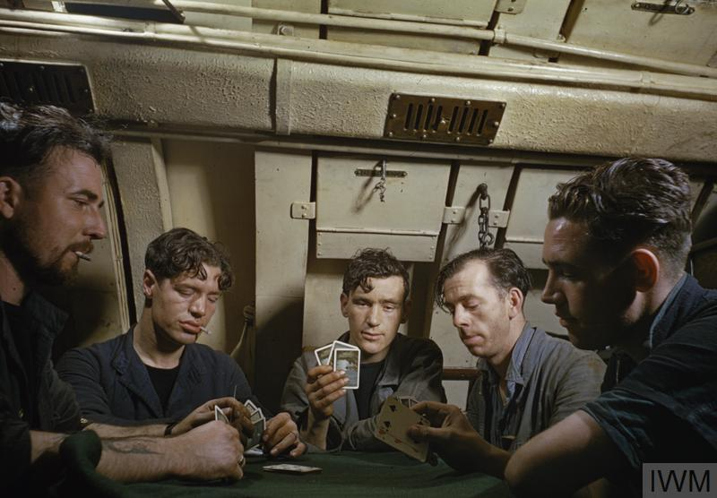 Men of the Royal Navy play cards on board the submarine HMS Tribune.
