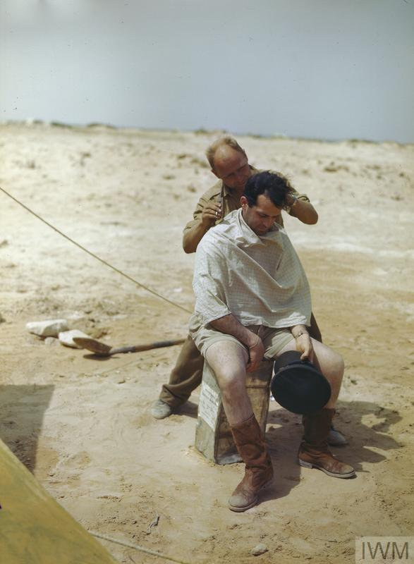 The Medical Officer of No 417 Squadron, Royal Canadian Air Force, Flight Lieutenant H J F Joncas, having a haircut while seated on a five-gallon can.