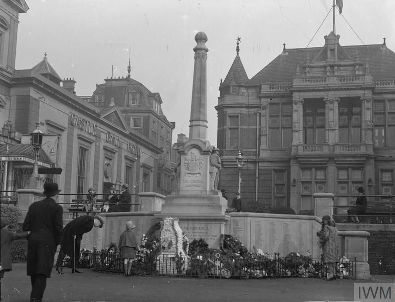 ca 1920s view of the War Memorial at Richmond, Surrey surrounded by wreaths with large buildings in the background