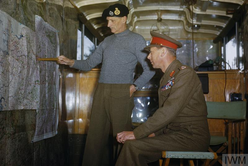 During a tour of the 2nd Army area, HM King George VI visited the headquarters of the Commander of the 21st Army Group, Field Marshal Sir Bernard Montgomery. Field Marshal Montgomery is shown explaining his future plans to the King in his map lorry.