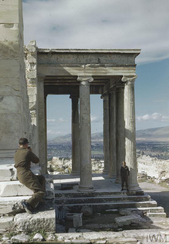 Sergeant R Gregory photographs Driver A Hardman on the Erectheum during a tour of the Acropolis in Athens.