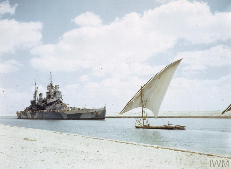 HMS HOWE, Flagship of the Commander in Chief, Pacific Fleet, Admiral Sir Bruce Fraser, passing through the Suez Canal on her way to join the British Pacific Fleet. In the foreground is an Egyptian felucca.
