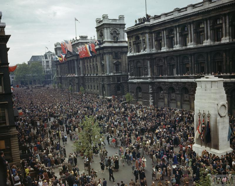 View of the crowd in front of the Ministry of Health building in Whitehall, 8 May 1945. The Prime Minister addressed the crowd from the balcony, which, like the roof of the building, is decorated with flags. On the right is the Cenotaph.
