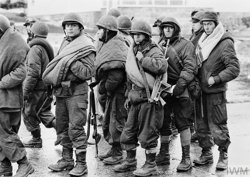 Argentine prisoners wait to hand in their weapons and other equipment at Port Stanley after the surrender. Most are carrying blankets.