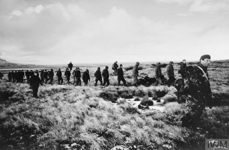 Captured Argentine prisoners are marched away from Goose Green under guard.