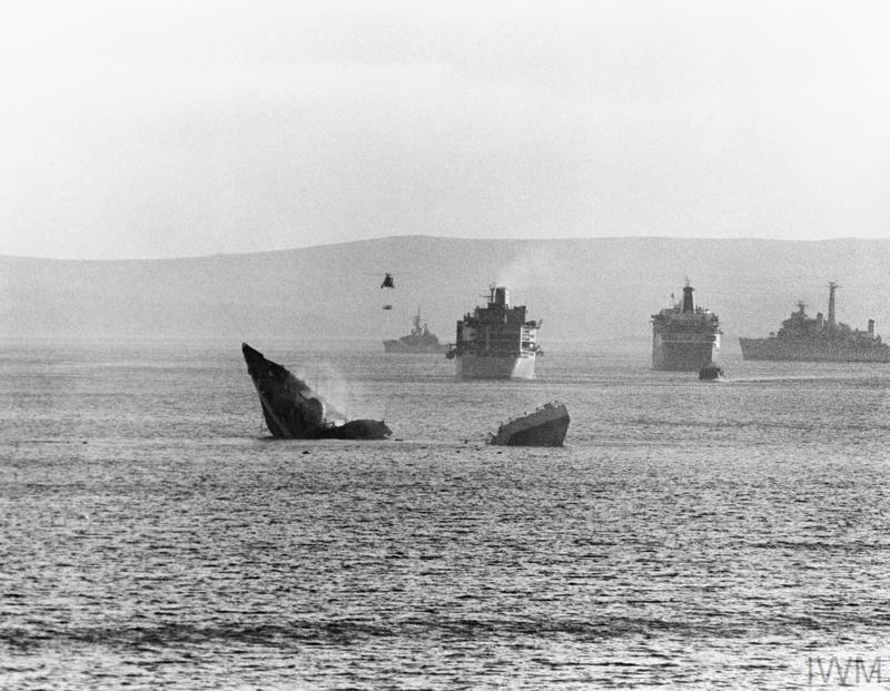 The bow and stern sections of HMS ANTELOPE float above the surface in San Carlos Water after the ship broke her back and sank on 24 May 1982.