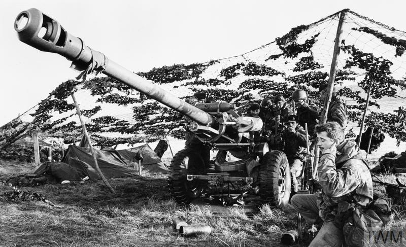 A 105 mm light gun of 29 Commando Regiment, Royal Artillery sited under camouflage netting between Fitzroy and Bluff Cove.