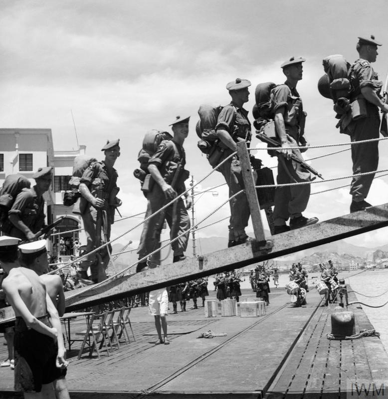 Men of the 1st Battalion, Argyll and Sutherland Highlanders boarding the cruiser HMS CEYLON for the journey to Pusan, South Korea. In the background the band of the King's Own Scottish Borderers play on.