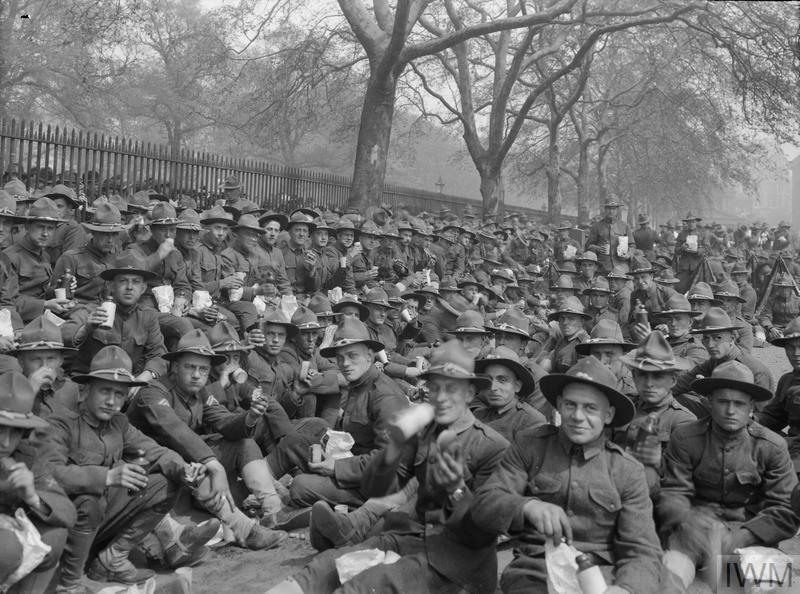 Soldiers of the American Expeditionary Forces, recently arrived in London, eat a packed lunch in a park shortly before parading in front of King George V and Queen Mary at Buckingham Palace in London, 13 May 1918.