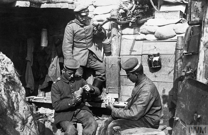 German troops playing cards in the trenches near Ypres. Note a Maxim machine gun ready for use over their heads.